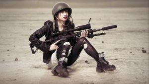 Is this what Jenny Who would look like? Woman in combat gear with gun sits on sand