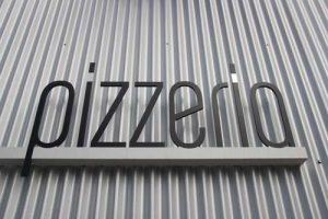 Pizzerias. We got 'em. Pizzeria sign against industrial backdrop.