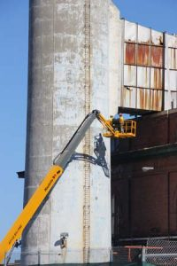 Shapes and shadows. Worker in boom lift alongside chimney.