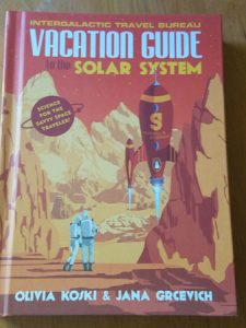 Grab your travel guide and suit up! Front cover of Vacation Guide to the Solar System