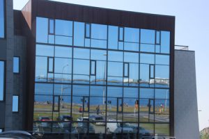 REflections of the waterfront in a glass office building.