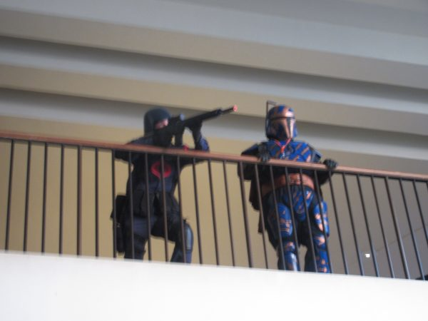 A couple of cosplayers pose on a balcony