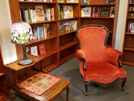 Orange chair with side table and lamp. Sit a spell, turn those pages and relax.