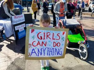 "You tell 'em, sister. Girl with ""Girls can do anything"" sign"