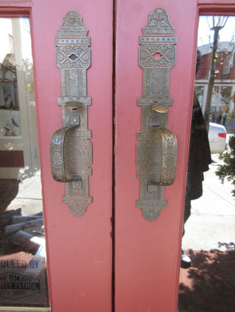 Fancy door handles on the building that houses several shops...
