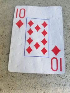 The Ten of diamonds, looking like it has been run over once or twice.