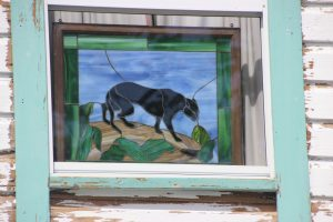 Black panther stained glass detail in a camp house.