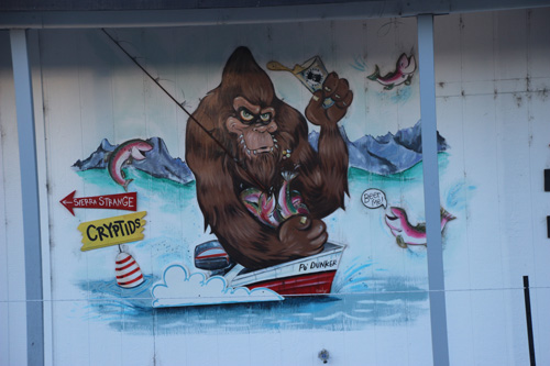 Mural Bigfoot drinking a beer and trout fishing.