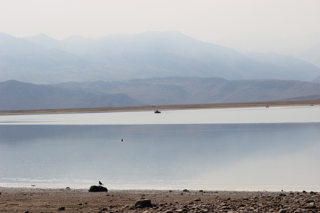 Expanse of lake with smoke obscuring the mountains.