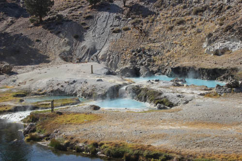 In a rocky terrain, three turquoise blue hot springs, steaming.