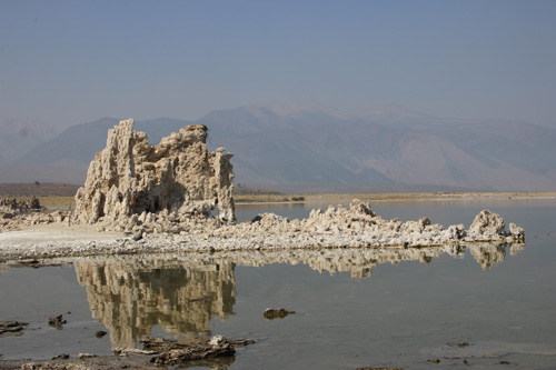 Limestone tufa tower on the shore reflected in water.