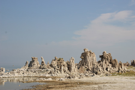 A row of tufa, looking like human figures, against a cloudy horizon.