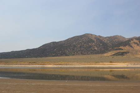 Reflection of hill and landscape in still water.