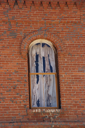 Ragged, spooky curtain on window in a red brick wall.