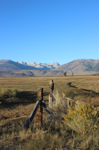The view west from Bridgeport, cliffs, pasture, wooden fence post in foreground